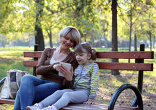 Mother and daughter play with tablet Stock Photos