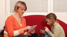 Mother and daughter play with tablet Stock Images