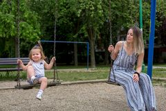 Mother and daughter at playground swinging Royalty Free Stock Photos