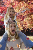 Mother and daughter playing in autumn leaves Royalty Free Stock Photo