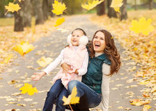 Mother and daughter playing in autumn park stock images