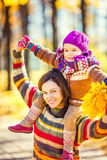 Mother and daughter playing in autumn park. Little girl playing with mother in the autumn park Royalty Free Stock Photos