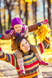 Mother and daughter in playing in autumn park Stock Images