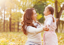 Mother and daughter playing in autumn park Royalty Free Stock Image