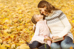 Mother and daughter playing in autumn park Stock Photo