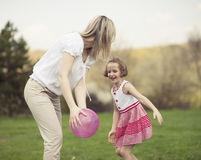 Mother and daughter playing with ball in the park Royalty Free Stock Photo