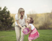 Mother and daughter playing with ball in the park Royalty Free Stock Image