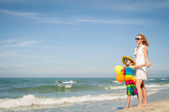 Mother and daughter playing with balloons on the beach at the da Royalty Free Stock Photos