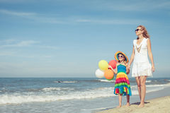 Mother and daughter playing with balloons on the beach at the da Stock Photo