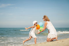 Mother and daughter playing with balloons on the beach at the da Stock Image