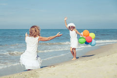 Mother and daughter playing with balloons on the beach at the da Royalty Free Stock Photography