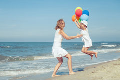 Mother and daughter playing with balloons on the beach at the da Stock Photos