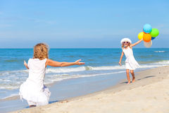 Mother and daughter playing with balloons on the beach at the da Royalty Free Stock Image