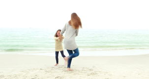 Mother and daughter playing on the beach stock footage