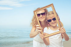 Mother and daughter playing on the beach at the day time. Stock Images