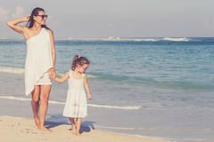 Mother and daughter playing on the beach at the day time. Royalty Free Stock Images
