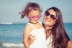 Mother and daughter playing on the beach at the day time. Stock Photo