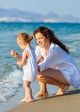Mother and daughter playing on the beach Stock Image