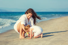 Mother and daughter playing on the beach Stock Photos