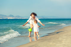 Mother and daughter playing on the beach Stock Photography