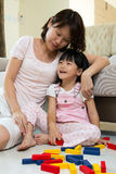 Mother and daughter playing blocks. Happy mother and daughter playing with colorful blocks inside a house Royalty Free Stock Photography
