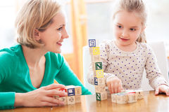Mother and daughter playing with blocks. Mother and daughter at home Stock Photos