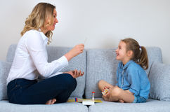 Mother and daughter playing board game. Mother and daughter playing board game at home Stock Images
