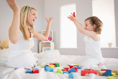 Mother and daughter playing with building blocks on bed Stock Photo
