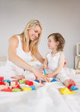 Mother and daughter playing with building blocks on bed Royalty Free Stock Images