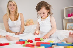 Mother and daughter playing with building blocks on bed Stock Image
