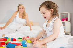Mother and daughter playing with building blocks on bed Stock Images