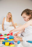 Mother and daughter playing with building blocks on bed Royalty Free Stock Photo