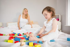 Mother and daughter playing with building blocks on bed Royalty Free Stock Photos