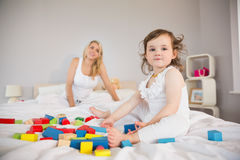 Mother and daughter playing with building blocks on bed Stock Photography