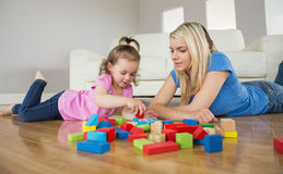 Mother and daughter playing with building blocks on floor Stock Photos