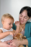 Mother and daughter playing with a cat stock images