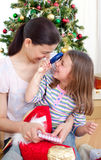 Mother and daughter playing with Christmas gifts Royalty Free Stock Photos