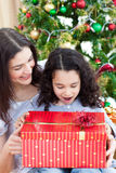 Mother and daughter playing with Christmas gifts Stock Images