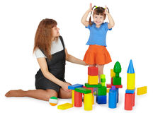 Mother and daughter playing with color blocks. Mother and daughter playing with colored blocks on a white background royalty free stock image