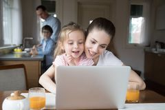 Mother and daughter playing computer while father and son cooking stock image