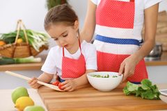 Happy family in the kitchen. Mother and child daughter cooking tasty breakfest of fresh salad. Little helper slicing an royalty free stock photography