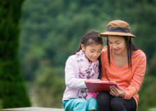 Mother and daughter playing with digital tablet. Royalty Free Stock Images