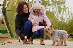 Mother and daughter playing with dog on playground.  Royalty Free Stock Photo