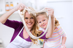 Mother and daughter playing with dough for donuts Royalty Free Stock Photography