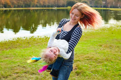 Mother and daughter playing with feathers in park Stock Photos