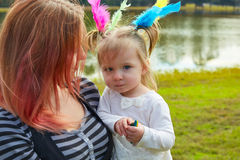 Mother and daughter playing with feathers in park Royalty Free Stock Images