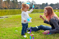 Mother and daughter playing with feathers in park Stock Images