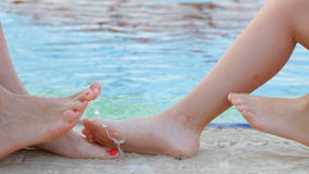 Mother and daughter playing feet of water near the pool.  stock footage