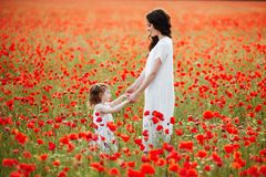 Mother and daughter playing in flower field Stock Photography