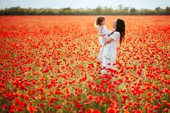 Mother and daughter playing in flower field stock photos
